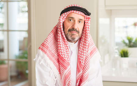 Middle age arabian man at home with a confident expression on smart face thinking serious