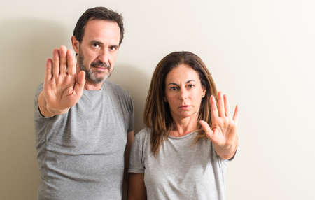 Middle age couple, woman and man with open hand doing stop sign with serious and confident expression, defense gesture 스톡 콘텐츠