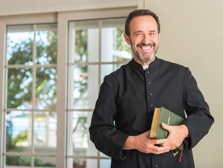 Chrześcijański ksiądz mężczyzna ze szczęśliwą twarzą stojącą i uśmiechniętą z pewnym siebie uśmiechem pokazującym zęby