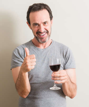 Senior man drinking red wine in a glass happy with big smile doing ok sign, thumb up with fingers, excellent sign 스톡 콘텐츠