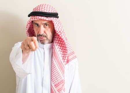 Senior arabic man pointing with finger to the camera and to you, hand sign, positive and confident gesture from the front