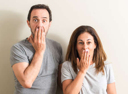 Middle age couple, woman and man cover mouth with hand shocked with shame for mistake, expression of fear, scared in silence, secret concept
