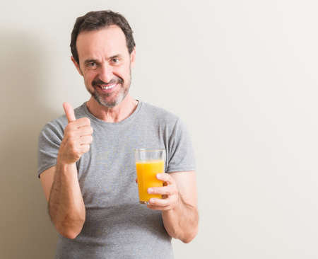 Senior man drinking orange juice in a glass happy with big smile doing ok sign, thumb up with fingers, excellent sign 스톡 콘텐츠