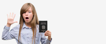 Young blonde toddler holding italian passport very happy and excited, winner expression celebrating victory screaming with big smile and raised hands