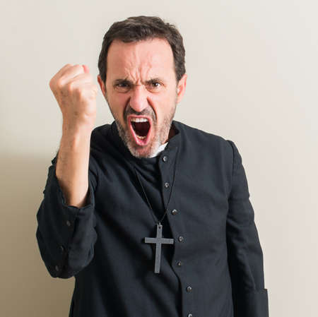 Senior priest religion man annoyed and frustrated shouting with anger, crazy and yelling with raised hand, anger concept