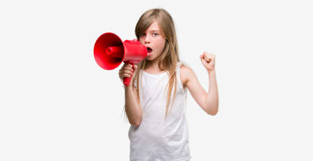 Young blonde toddler holding megaphone annoyed and frustrated shouting with anger, crazy and yelling with raised hand, anger concept Standard-Bild
