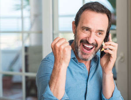 Middle age man using smartphone screaming proud and celebrating victory and success very excited, cheering emotion