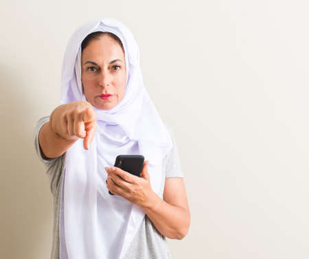 Arabian woman using smartphone pointing with finger to the camera and to you, hand sign, positive and confident gesture from the front