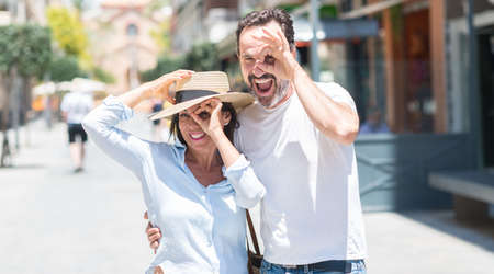 Middle age couple down the street with happy face smiling doing ok sign with hand on eye looking through fingers