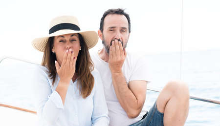 Middle age couple traveling on sailboat cover mouth with hand shocked with shame for mistake, expression of fear, scared in silence, secret concept Imagens