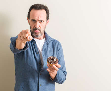 Senior man eating chocolate donut pointing with finger to the camera and to you, hand sign, positive and confident gesture from the front