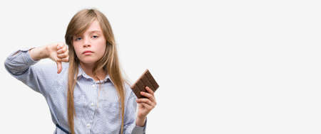 Young blonde child holding chocolate bar with angry face, negative sign showing dislike with thumbs down, rejection concept Imagens