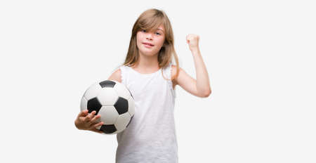 Young blonde toddler holding football ball screaming proud and celebrating victory and success very excited, cheering emotion