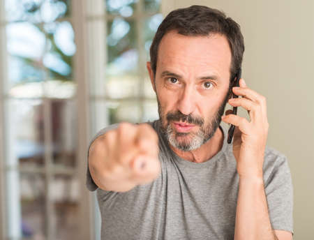 Middle age man using smartphone pointing with finger to the camera and to you, hand sign, positive and confident gesture from the front Foto de archivo