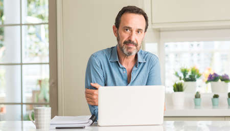 Middle age man using laptop at home with a confident expression on smart face thinking serious
