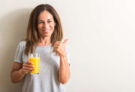 Middle age woman drinking orange juice in a glass happy with big smile doing ok sign, thumb up with fingers, excellent sign
