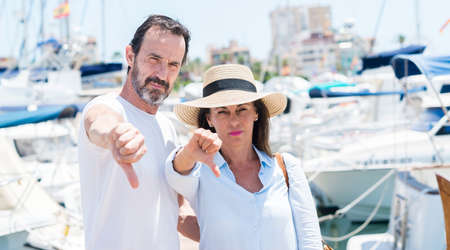 Middle age couple in marina with angry face, negative sign showing dislike with thumbs down, rejection concept Banco de Imagens