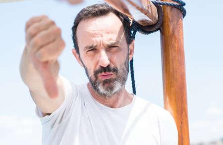 Handsome senior man traveling on sailboat with angry face, negative sign showing dislike with thumbs down, rejection concept