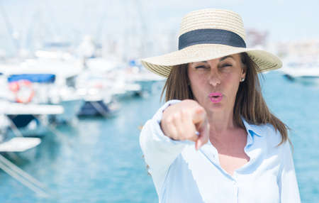 Beautiful middle age woman standing with the sea in the background pointing with finger to the camera and to you, hand sign, positive and confident gesture from the front