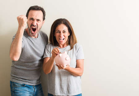 Middle age couple, woman and man, holding piggy bank annoyed and frustrated shouting with anger, crazy and yelling with raised hand, anger concept