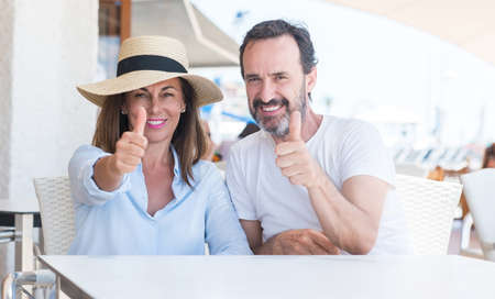 Middle age couple sitting at terrace happy with big smile doing ok sign, thumb up with fingers, excellent sign