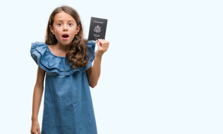 Brunette hispanic girl holding passport of United States of America scared in shock with a surprise face, afraid and excited with fear expression