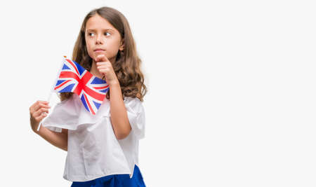 Brunette hispanic girl holding flag of United Kingdom serious face thinking about question, very confused idea