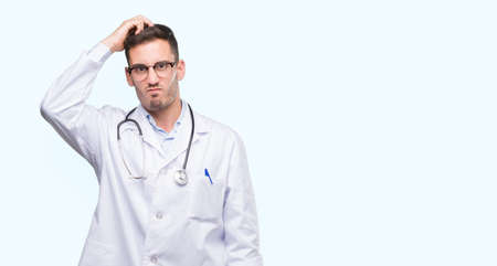 Handsome young doctor man confuse and wonder about question. Uncertain with doubt, thinking with hand on head. Pensive concept. Stock Photo
