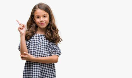 Ragazza bruna ispanica che indossa un abito bianco e nero molto felice che punta con la mano e il dito di lato