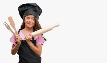 Brunette hispanic girl wearing cook uniform with a happy face standing and smiling with a confident smile showing teeth Stock Photo