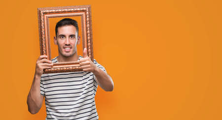 Handsome young man looking through vintage art frame happy with big smile doing ok sign, thumb up with fingers, excellent sign