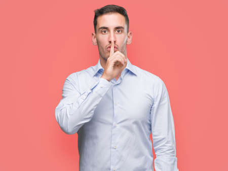 Handsome young businessman asking to be quiet with finger on lips. Silence and secret concept.