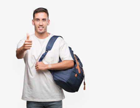 Handsome young man holding backpack happy with big smile doing ok sign, thumb up with fingers, excellent sign
