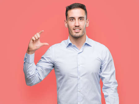 Handsome young businessman smiling and confident gesturing with hand doing size sign with fingers while looking and the camera. Measure concept.