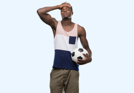 Young african american man holding soccer football ball stressed with hand on head, shocked with shame and surprise face, angry and frustrated. Fear and upset for mistake. Stock Photo