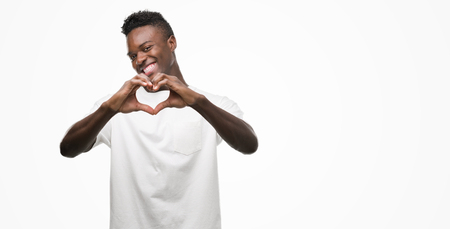 Young african american man wearing white t-shirt smiling in love showing heart symbol and shape with hands. Romantic concept. Stock Photo
