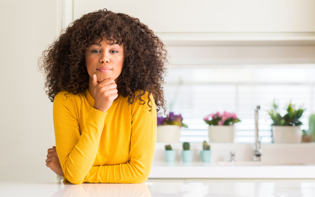 African american woman wearing yellow sweater at kitchen looking confident at the camera with smile with crossed arms and hand raised on chin. Thinking positive.