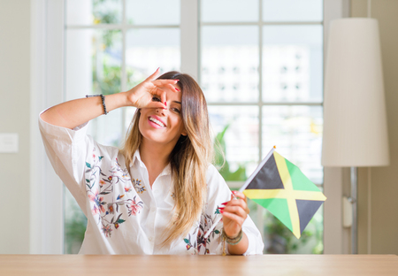 Young woman at home holding flag of Jamaica with happy face smiling doing ok sign with hand on eye looking through fingers