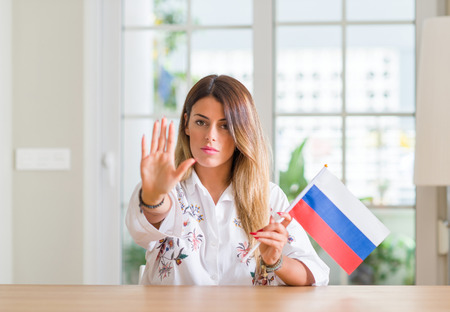 Young woman at home holding flag of Russia with open hand doing stop sign with serious and confident expression, defense gesture Stock Photo