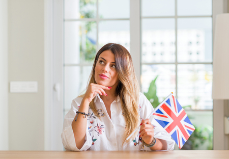 Young woman at home holding flag of United Kingdom serious face thinking about question, very confused idea Banque d'images - 105317303