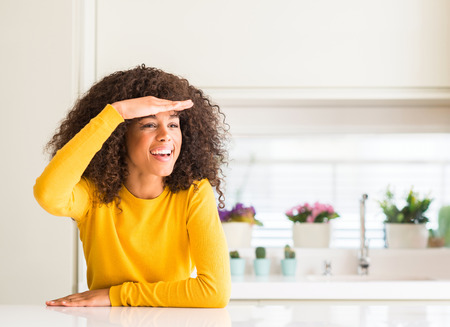 African american woman wearing yellow sweater at kitchen very happy and smiling looking far away with hand over head. Searching concept.