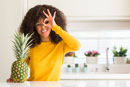 African american woman and pineapple tropical fruit with happy face smiling doing ok sign with hand on eye looking through fingers Foto de archivo