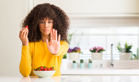 African american woman eating strawberries at home with open hand doing stop sign with serious and confident expression, defense gesture