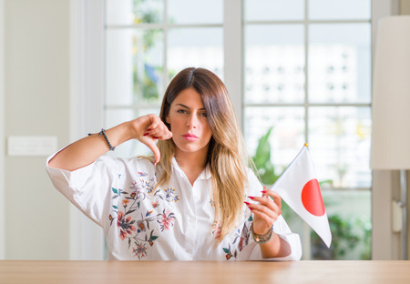 Young woman at home holding flag of Japan with angry face, negative sign showing dislike with thumbs down, rejection concept