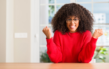 African american woman wearing glasses screaming proud and celebrating victory and success very excited, cheering emotion