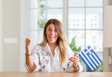 Young woman at home holding flag of Greece screaming proud and celebrating victory and success very excited, cheering emotion