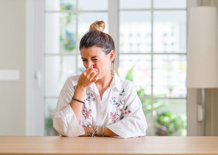 Mujer joven en casa oliendo algo apestoso y repugnante, un olor intolerable, conteniendo la respiración con los dedos en la nariz. Concepto de malos olores.