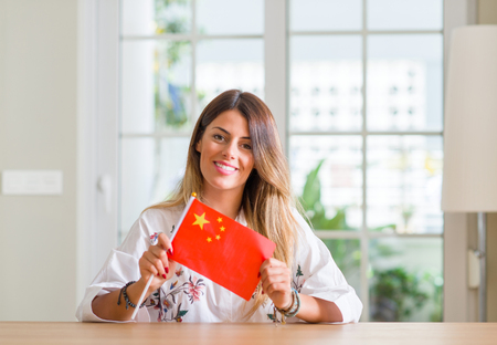 Young woman at home holding flag of China with a happy face standing and smiling with a confident smile showing teeth