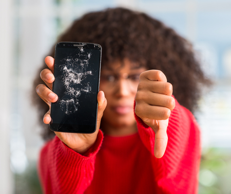 African american woman holding broken smartphone with angry face, negative sign showing dislike with thumbs down, rejection concept