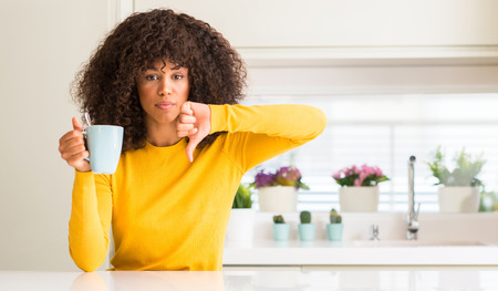 Beautiful african american woman holding a cup of coffee at home with angry face, negative sign showing dislike with thumbs down, rejection concept Stockfoto